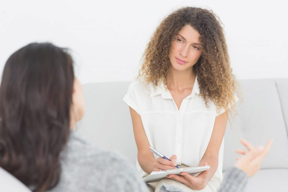 Serious therapist listening to her talking patient at therapy session